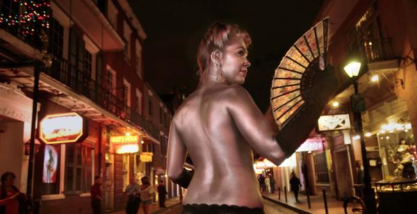 Performer  Holly Hawthorne sports a coat of silver paint on Bourbon Street, which is best explored after the sun goes down. In daylight, the street in the French Quarter can just look tawdry.
