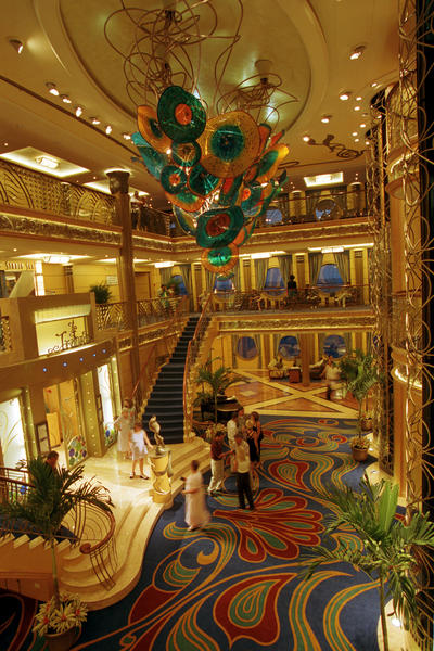 "The three-deck atrium lobby on the Disney Wonder features Art Nouveau-inspired details reminiscent of the Golden Age of cruising. A bronze statue of Ariel from the classic Disney film ""The Little Mermaid"" is a focal point and a favorite photo location for guests. (©Disney)"