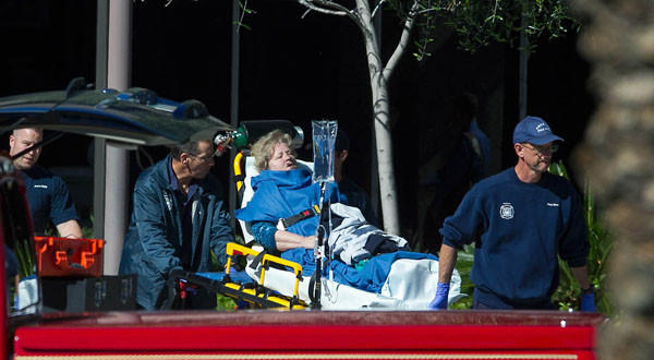 A woman is taken to a paramedic truck from an office building where a shooter opened fire in north central Phoenix.