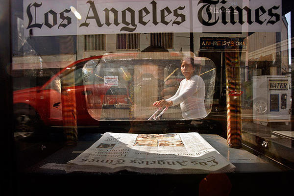 A pedestrian looks at a Los Angeles Times news rack.