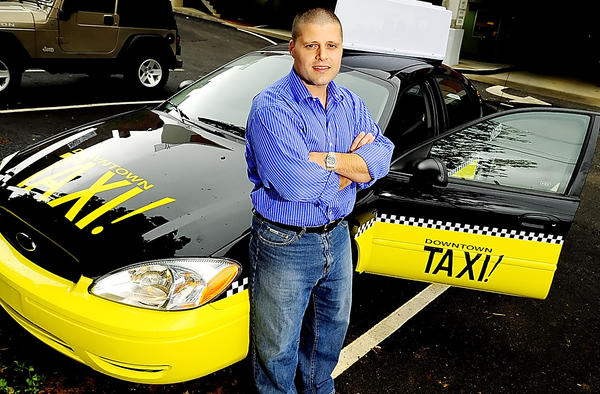In this 2008 file photo, Mike Deming, President of Demcore Development is shown with one of his Downtown Taxi cabs. Deming wants to start a Tipsy Taxi service to cut down on the number of drunk drivers.