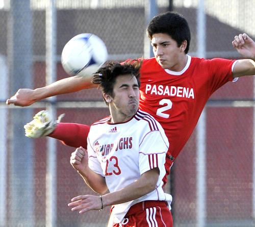 Pasadena's Alejandro Loeza  high kicks to clear the ball passed the attack of Burroughs' Brandon Gerlach in the second half in a Pacific League boys soccer match at Burroughs High School in Burbank on Monday, January 28, 2013. Pasadena won the match 3-1.