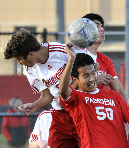 Pasadena's Gerardo Espinoza leaps with Burroughs' Xavi Izqueta and teammate Alejandro Loeza to head a corner kick in the second half in a Pacific League boys soccer match at Burroughs High School in Burbank on Monday, January 28, 2013. Pasadena won the match 3-1.
