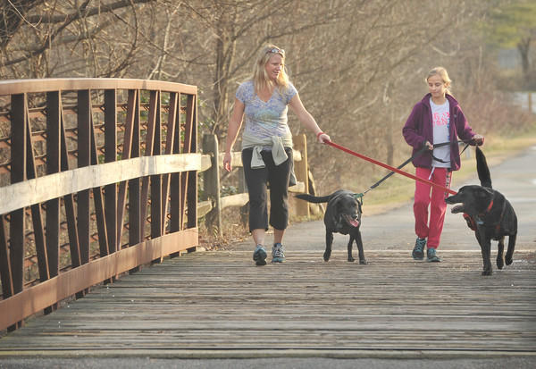Patti Ringers, left, and her daughter Macy Iams, of Severna Park, walk their dogs on the trail at Kinder Farm Park on a mild afternoon Tuesday.