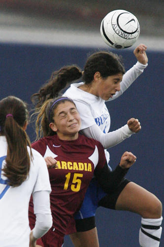 Burbank's Zana Hundal jumps higher to head the ball against Arcadia's Vienna Rousset in the first half in a Pacific League girls soccer match at Burbank High School on Friday, February 25, 2013.