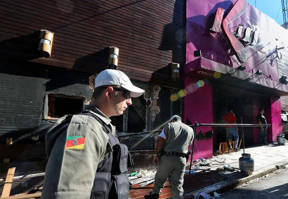 Policemen check the Kiss nightclub in Santa Maria, Brazil, where a blaze killed 235 people. Police have arrested four suspects -- two of the club's owners and two members of a band that staged a pyrotechnics show -- but some Brazilians say city officials are also culpable for allowing safety rules to be ignored.