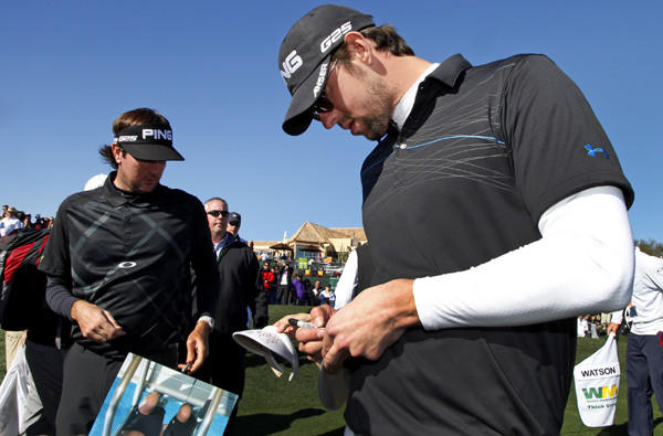 Michael Phelps signs an autograph as he and playing partner Bubba Watson leave the 18th green in Scottsdale, Ariz.