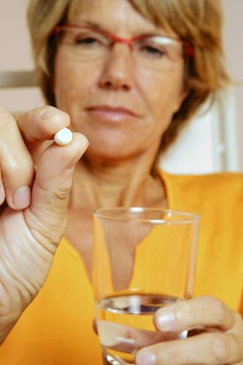 Woman taking medication as part of hormone replacement therapy
