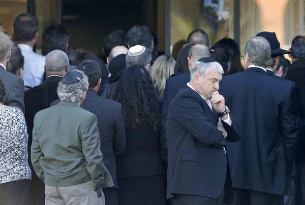 Mourners gather outside the doors and listen to prayer during a memorial service for Dr. Ronald Gilbert at the Harbor Lawn-Mt. Olive Memorial Park & Mortuary on Wednesday.