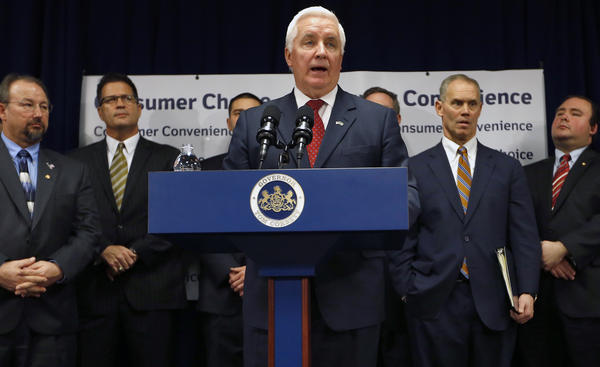 Pennsylvania Gov. Tom Corbett, center, stands with a group of colleagues as he addresses a news conference in Pittsburgh, where he announced his plan to privatize the liquor system in Pennsylvania  on Wednesday. Corbett said the plan commits $1 billion in proceeds from the process to education funding.