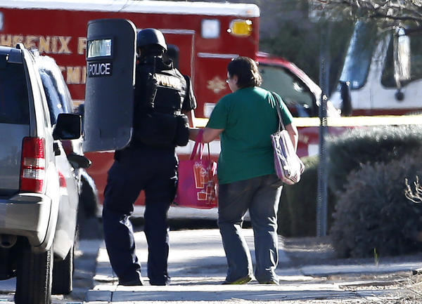 A member of the Phoenix Police Department SWAT team leads a female neighbor to safety as the SWAT team prepares to enter the home of a suspect in the shooting at a Phoenix office building.