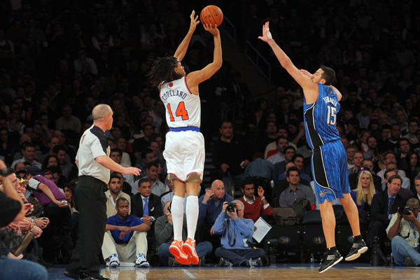 New York Knicks forward Chris Copeland (14) shoots a three-point shot over Orlando Magic forward Hedo Turkoglu (15) during the second quarter of an NBA game at Madison Square Garden.