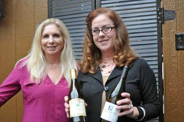 Greeting guests are, from left, Lora Taylor of Demetria Winery, and Leslie Farrell of Richard Grant and Baletto Wineries.