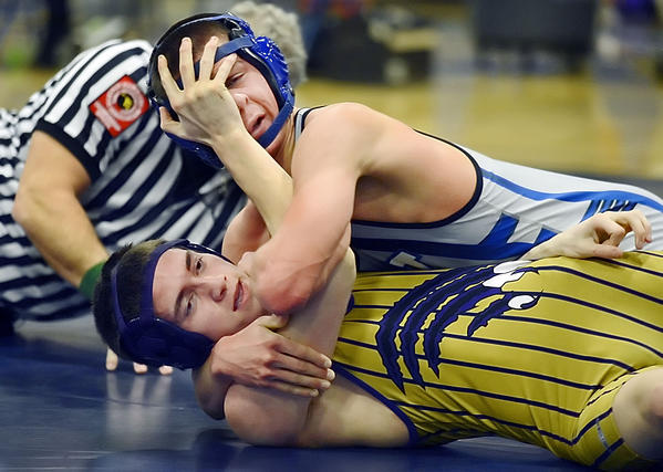 Smithsburg's Eric Janisko, bottom, gets a hand in the face of Williamsport's Sinjin Shoop during their 138-pound bout on Wednesday.