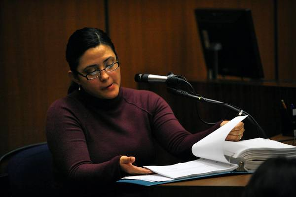 Bell City Clerk Rebecca Valdez leafs through paperwork for a specific exhibit at the 2011 preliminary hearing for two former Bell officials accused of corruption. Testifying Wednesday at the trial of six former council members, she said the signatures on many city documents were forged.