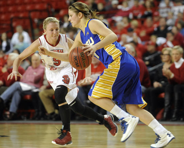 SDSU's Tar Heiser (12) drives down the court against USD's Alexis Yackley (5) during women's basketball in Vermillion on Wednesday.