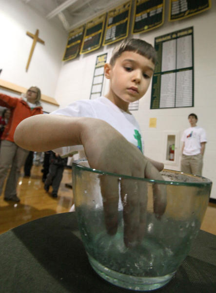 Adam Mitzel, 8, a second-grader at Roncalli Primary School, dips into the bowl of holy water as he entered the Roncalli High School gym for Wednesday's All-School Mass in celebration of National Catholic Schools Week. American News Photo by John Davis
