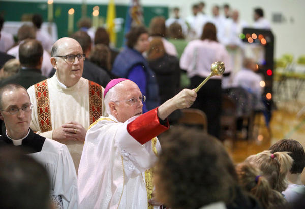 Bishop Paul Swain, center, conducts Mass with the assistance of Deacon Peter Mehlhaff, back left and Father Justin Wachs, far left, during Wednesday's Roncalli All School Mass at the Roncalli High School gym. The mass was part of the National Catholic Schools Week celebration. American News Photo by John Davis