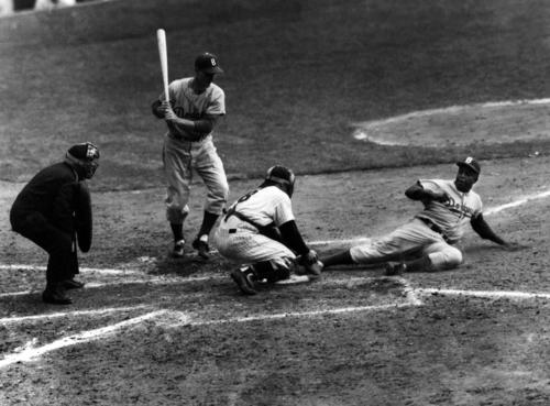 Jackie Robinson safely steals home under the tag of Yankees catcher Yogi Berra in the eighth inning of the 1955 World Series opener at Yankee Stadium. The Dodgers would win the championship in seven games, the first in franchise history and only title for Brooklyn.