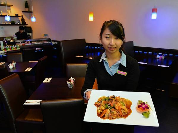 Ling Liu holds a dish of The Wok Basil Fio, featuring chicken, beef, and shrimp with vegetables in a fresh basil leaf brown sauce at Ginger Asian Cuisine & Sushi Bar in Macungie.