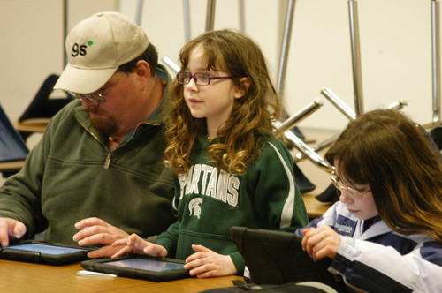 Serina (right) and Megen Trarop accompany their father, Tod, in an iPad valentine-making class. The class was one of several Wednesday at Boyne City Public Schools' tech night, which was open to parents, students and the public.