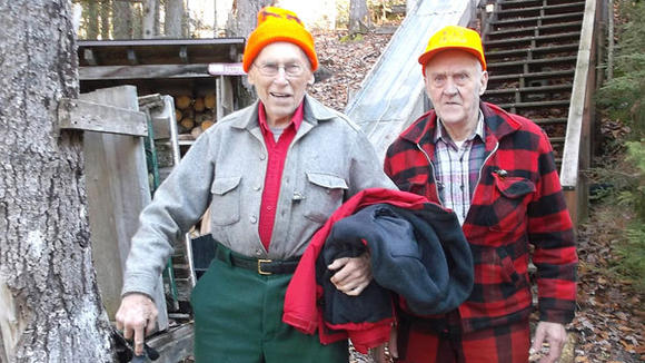 Ken Teysen (left) and Tom Alexander, both 91 and Mackinaw City residents, pause at the base of a set of stairs at their hunting camp, the Tahquamenon Club, in the Upper Peninsula.