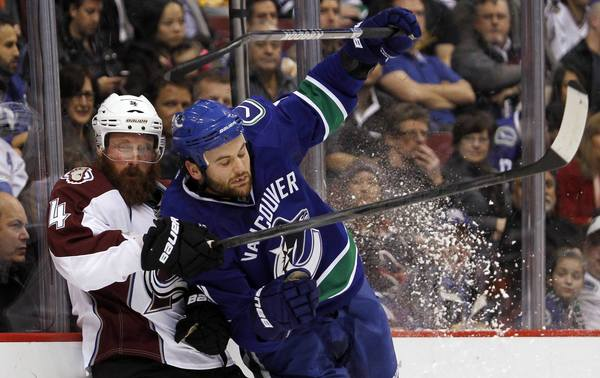 Vancouver Canucks Zack Kassian (R) checks Greg Zanon of the Colorado Avalanche during the first period of their NHL hockey game in Vancouver, British Columbia January 30, 2013.