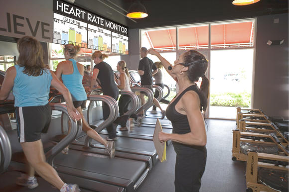 Participants run and walk on the treadmills during a class at Orange Theory Fitness in Newport Beach.