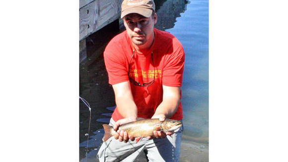 Jason Tucker of Alanson shows off a fly-caught coaster brook trout landed in Tobin Harbor on Isle Royale.