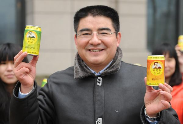 Chen Guangbiao hands out cans of fresh air in a financial district in Beijing.