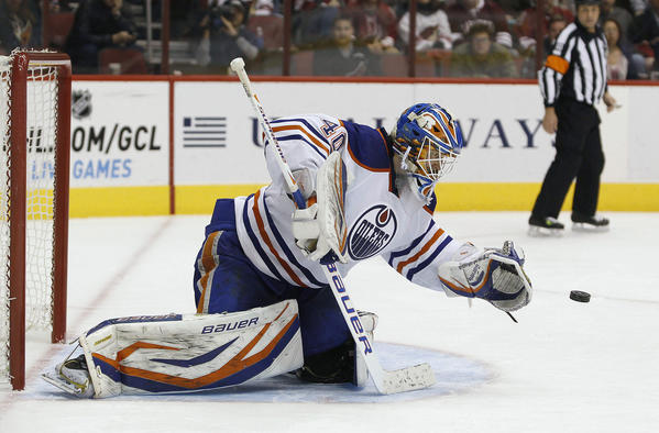 Edmonton Oilers goalie Devan Dubnyk (40) tries to cover up the puck after blocking a shot during third period action of their NHL hockey game against the Phoenix Coyotes.