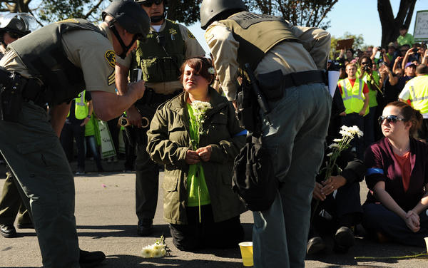 A protester about to be arrested outside a Wal-Mart in Paramount on Black Friday.