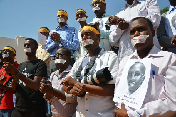 Somali journalists hold up the picture of arrested journalist Abdiaziz Abdinur Ibrahim at an event condemning his detention Sunday in Mogadishu.