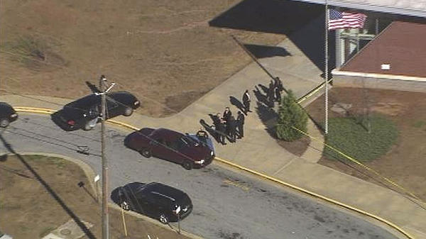 "In this image made from video and released by WSB-TV, authorities investigate the scene of a school shooting, Thursday in Atlanta. Authorities say a 14-year-old has been wounded in a shooting at an Atlanta middle school and a suspect has been taken into custody. Atlanta police spokesman Carlos Campos says the wounded student has been taken ""alert, conscious and breathing"" to Grady Hospital."