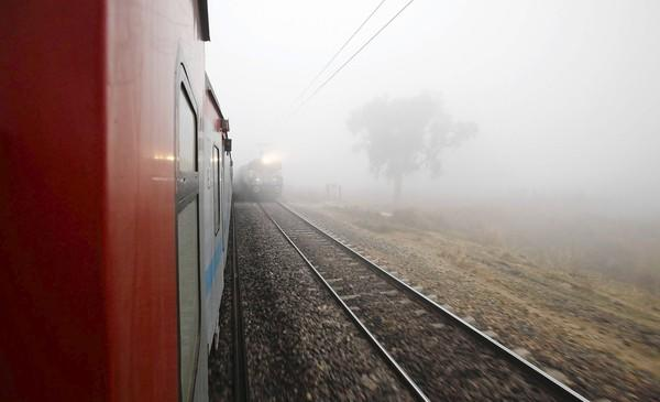 Trains pass in the fog outside Allahabad, India.