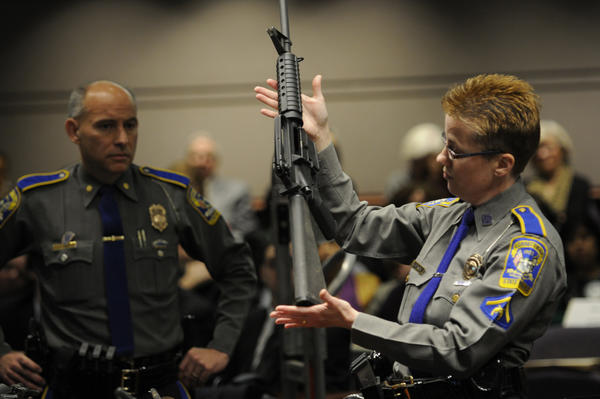 Detective Barbara Mattson of the Connecticut State Police displays a Bushmaster semi-automatic weapon during a hearing at the Legislative Office Building in Hartford on Jan. 28.