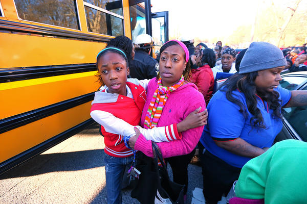 Tiffany Myricle, 37, leads her daughter Xavia Denise Myricle away from her school bus after a shooting at Price Middle School in Atlanta.