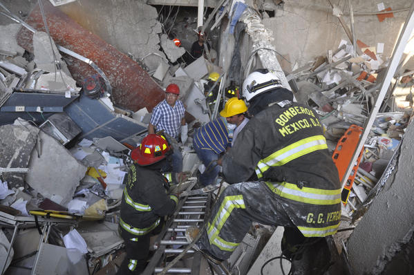 Firefighters belonging to the Tacubaya sector and workers dig for survivors after an explosion at an adjacent building to the executive tower of Mexico's state-owned oil company PEMEX, in Mexico City, Thursday. A large explosion occurred in the lower floors of the building and dozens have been reported injured so far.