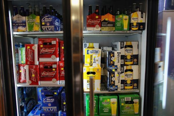 A cooler holds Anheuser-Busch's Budweiser and Grupo Modelo's Corona Light beers at the Chandi Wine and spirits store Thursday in Miami. The Justice Department filed suit to stop Anheuser-Busch InBev's $20.1-billion takeover of Grupo Modelo.