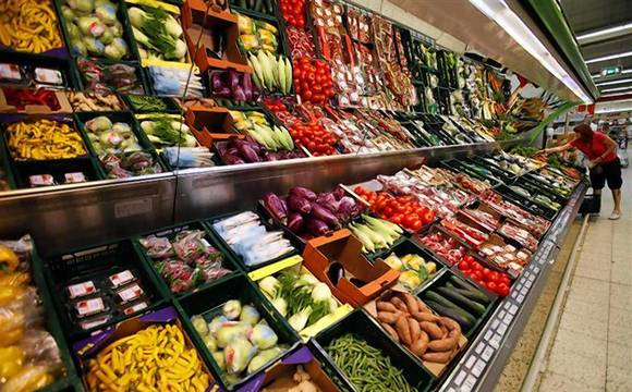 A customer selects vegetables at a supermarket in Prague
