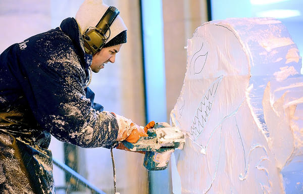 Ice Sculptor James Kowalczuk, from DiMartino Ice Co. of Jeannette, Pa., carves a dragon from several blocks of ice Thursday night during the opening night of IceFest in downtown Chambersburg.