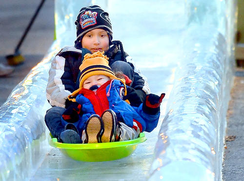 Antonio Santiago, rear, 8, and his brother, Giovanni George, front, 3, ride the Ice Slide together Thursday night during the opening night of the annual IceFest in downtown Chambersburg, Pa.