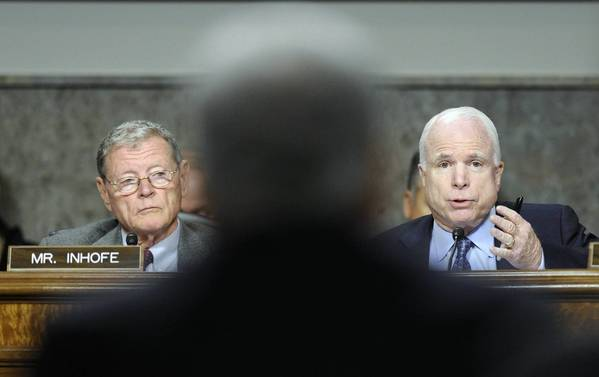 Sen. John McCain questions his former GOP colleague Chuck Hagel during the Senate Armed Services Committee hearing on Hagel's nomination to be Defense secretary. Sen. James Inhofe (R-Okla.) listens.