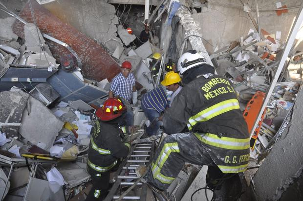 Firefighters and workers dig for survivors after an explosion next to the executive tower in the headquarters complex of Pemex, Mexico's state-owned oil company,in Mexico City.