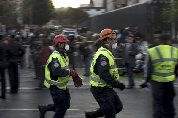 Rescue workers head for the skyscraper that houses the headquarters of state-owned Mexican oil giant Pemex in Mexico City after an explosion.