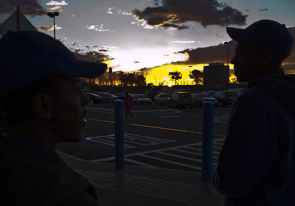 Two Walmart Supercenter employees wait in the early morning light for the opening of the new 150,000-square-foot store in Newport News Friday morning.