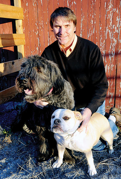 Opie the bouvier des Flanders, left, and Hannah the bulldog comfort author and Herald-Mail columnist Tim Rowland in the dawns early light of his farmette. Rowlands most recent book, Creature Feature, is a compilation of comical columns featuring Opie, Hannah and dozens of other farm critters.