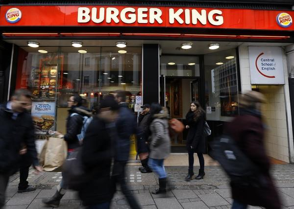 Pedestrians pass by a branch of Burger King in central London.