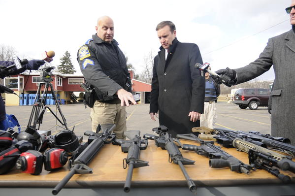 State police Sgt. Shawn Corey describes several different military style weapons to Sen. Chris Murphy during a demonstration at a state police firing range in Simsbury.