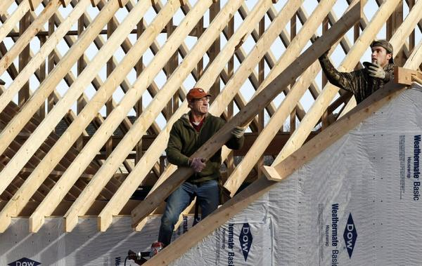 Construction workers build a home in Pepper Pike, Ohio, in December. The Commerce Department said Friday that construction spending increased 0.9% in December from the previous month.